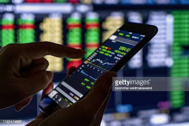 making trading online on the smart phone. new ways to make economy and trading - globalization economy stock pictures, royalty-free photos & images
