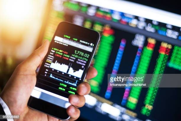 making trading online on the smart phone. new ways to make economy and trading - stock trader stock pictures, royalty-free photos & images