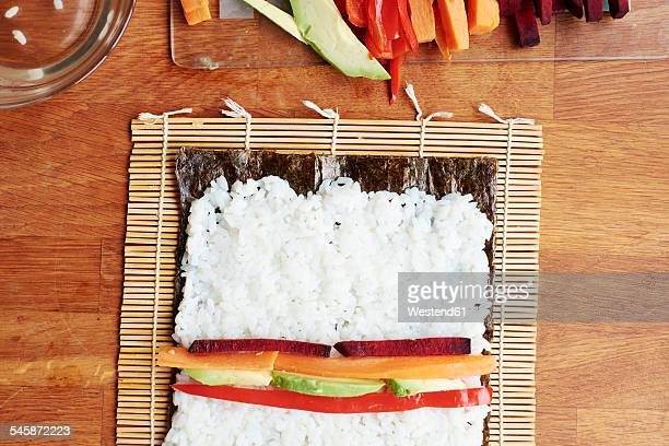 Making vegetable sushi with rice on a nori sheet