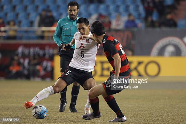Makino Tomoaki of Urawa Red Diamonds competes for the ball with Choe HoJu of Pohang Steelers during the AFC Champion League Group H match between...
