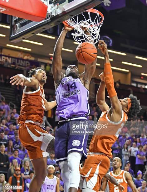 Makol Mawien of the Kansas State Wildcats scores with a dunk between Royce Hamm Jr. #5 and Kai Jones of the Texas Longhorns during the second half at...