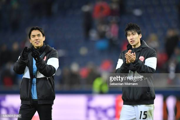 Makoto Hasebe and Daichi Kamada of Frankfurt talk after the UEFA Europa League round of 16 second leg match between RB Salzburg and Eintracht...