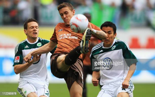 Makoto Hasebe and Sascha Riether of Wolfsburg and Max Kruse of Hamburg battle for the ball during the Bundesliga match between VfL Wolfsburg and FC...
