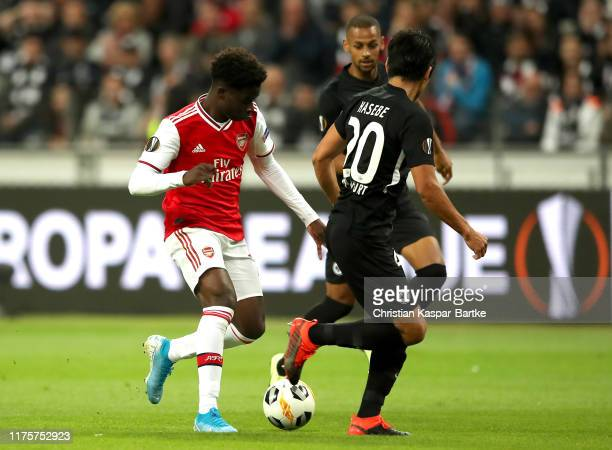 Makoto Hasebe of Eintracht Frankfurt attempts to tackle Bukayo Saka of Arsenal during the UEFA Europa League group F match between Eintracht...