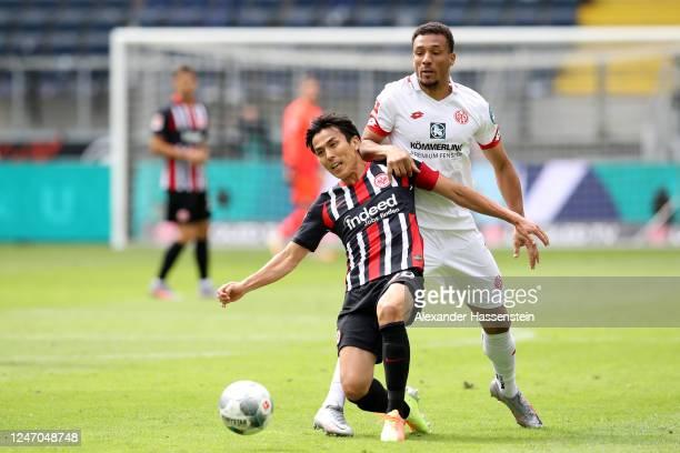 Makoto Hasebe of Eintracht Frankfurt is challenged by Karim Onisiwo of 1. FSV Mainz 05 during the Bundesliga match between Eintracht Frankfurt and 1....