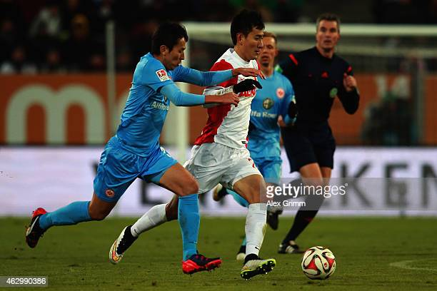 Makoto Hasebe of Frankfurt is challenged by DongWon Ji of Augsburg during the Bundesliga match between FC Augsburg and Eintracht Frankfurt at SGL...