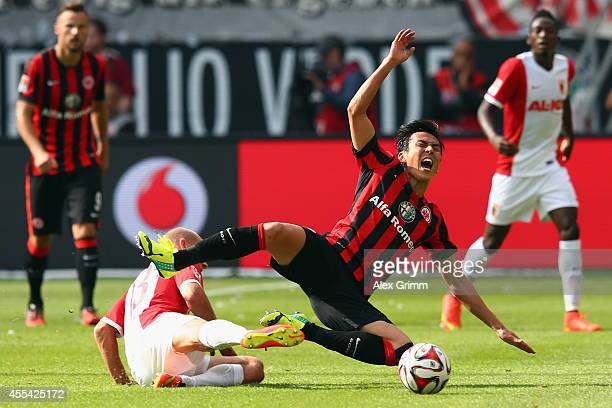 Makoto Hasebe of Frankfurt is challenged by Tobias Werner of Augsburg during the Bundesliga match between Eintracht Frankfurt and FC Augsburg at...