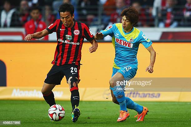 Makoto Hasebe of Frankfurt is challenged by Yuya Osako of Koeln during the Bundesliga match between Eintracht Frankfurt and 1 FC Koeln at...