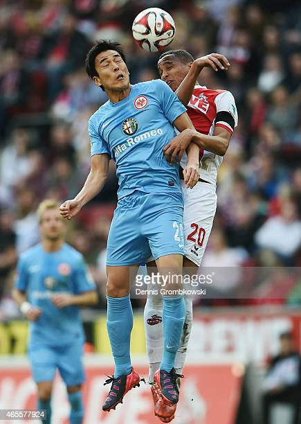 Makoto Hasebe of Frankfurt jumps for a header with Deyverson of Koeln during the Bundesliga match between 1 FC Koeln and Eintracht Frankfurt at...