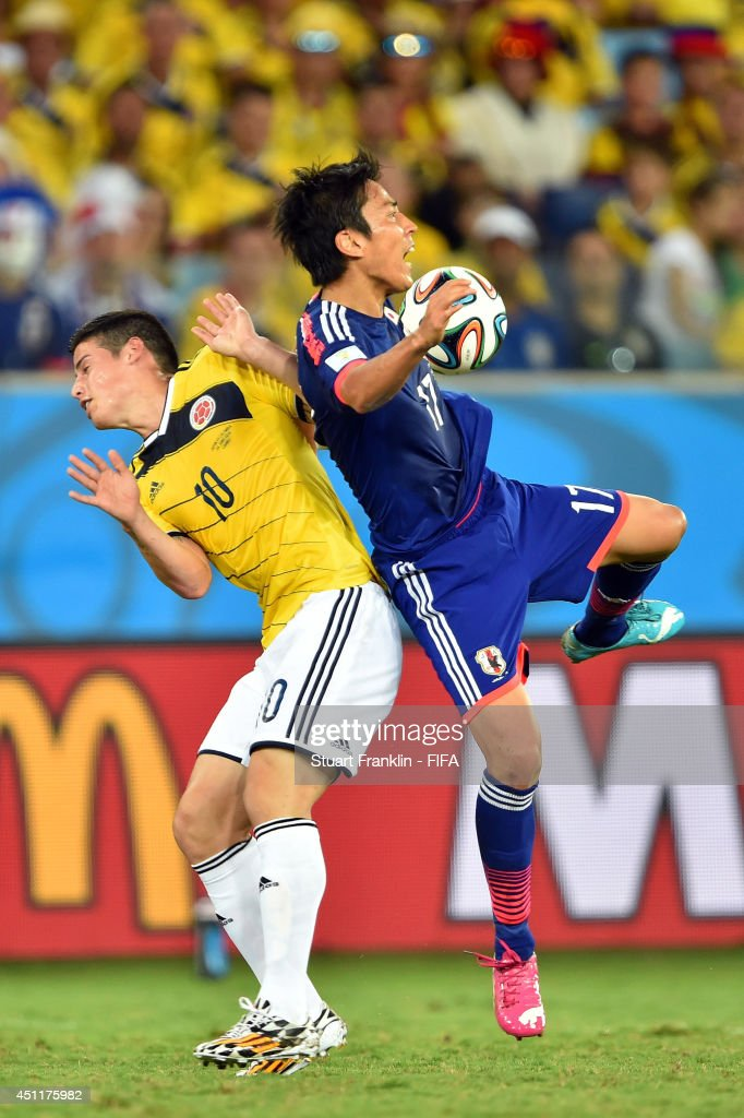 Makoto Hasebe of Japan and James Rodriguez of Colombia compete for the ball during the 2014 FIFA World Cup Brazil Group C match between Japan and Colombia at Arena Pantanal on June 24, 2014 in Cuiaba, Brazil.