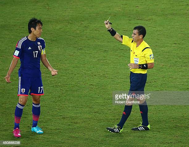 Makoto Hasebe of Japan is shown a yellow card by referee Joel Aguilar during the 2014 FIFA World Cup Brazil Group C match between Japan and Greece at...