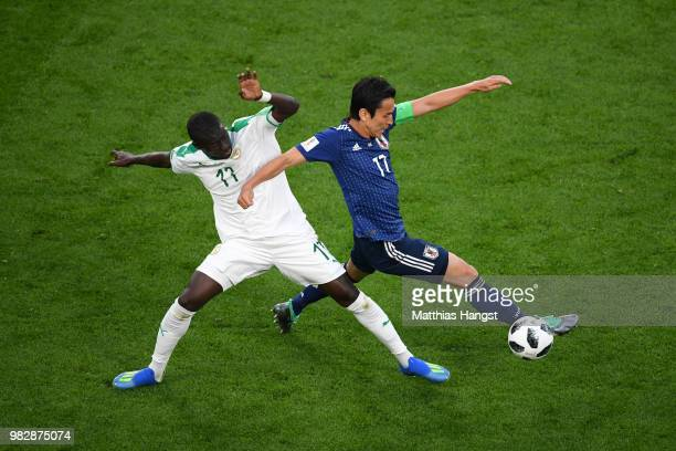 Makoto Hasebe of Japan is tackled by Pape Alioune Ndiaye during the 2018 FIFA World Cup Russia group H match between Japan and Senegal at...