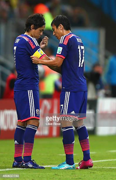 Makoto Hasebe of Japan passes the captain's armband to teammate Yasuhito Endo as he is subbed out during the 2014 FIFA World Cup Brazil Group C match...