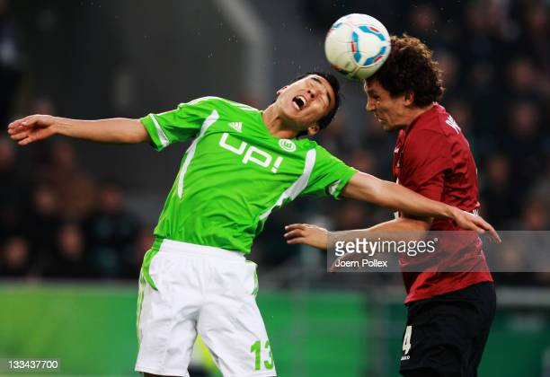 Makoto Hasebe of Wolfsburg and Emanuel Pogatetz of Hannover battle for the ball during the Bundesliga match between VfL Wolfsburg and Hannover 96 at...