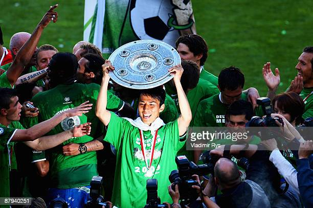 Makoto Hasebe of Wolfsburg celebrates the German Championship with the trophy after his Bundesliga match between VfL Wolfsburg and SV Werder Bremen...