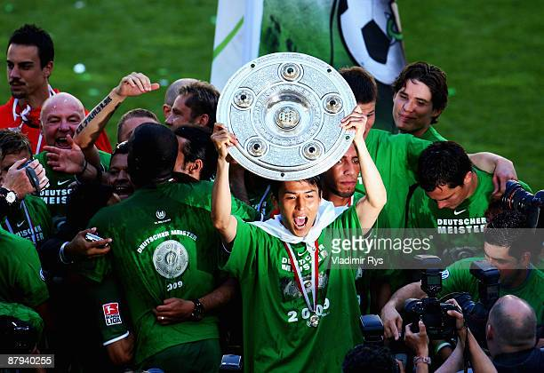 Makoto Hasebe of Wolfsburg celebrates the German Championship with the trophy after his Bundesliga match between VfL Wolfsburg and SV Werder Bremen...
