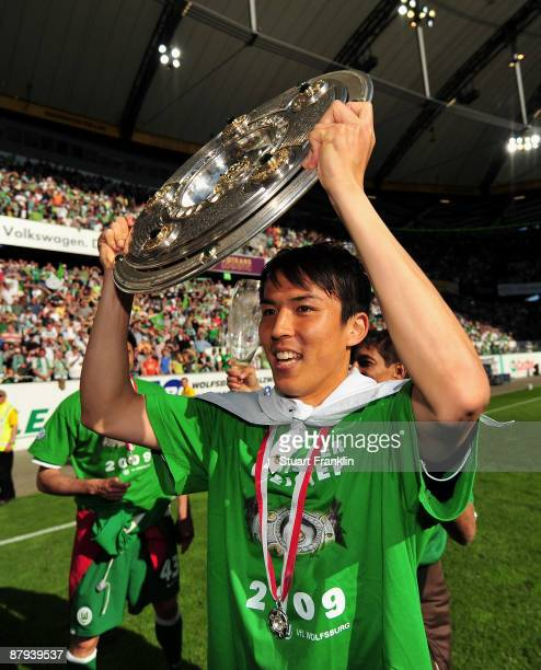 Makoto Hasebe of Wolfsburg lifts the German Championship trophy after the Bundesliga match between VfL Wolfsburg and Werder Bremen at the Volkswagen...