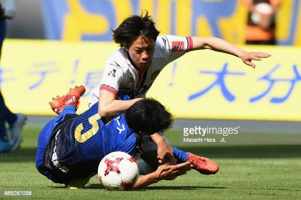 Makoto Mimura of Fagiano Okayama and Yoshinori Suzuki of Oita Trinita compete for the ball during the JLeague J2 match between Oita Trinita and...