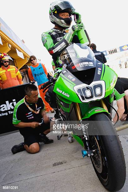 Makoto Tamada of Japan and Kawasaki World Superbike RT waits as his mechanics work during the SuperBike World Championship qualifying session on...