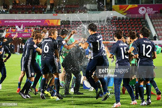 Makoto Teguramori Head coach of Japan is poured water by his players to celebrate qualifying for the Rio de Janeiro Olympics after winning the AFC...