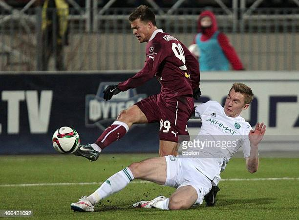 Maksim Kanunnikov of FC Rubin Kazan is challenged by Andrei Semyonov of FC Terek Grozny during the Russian Premier League match between FC Rubin...
