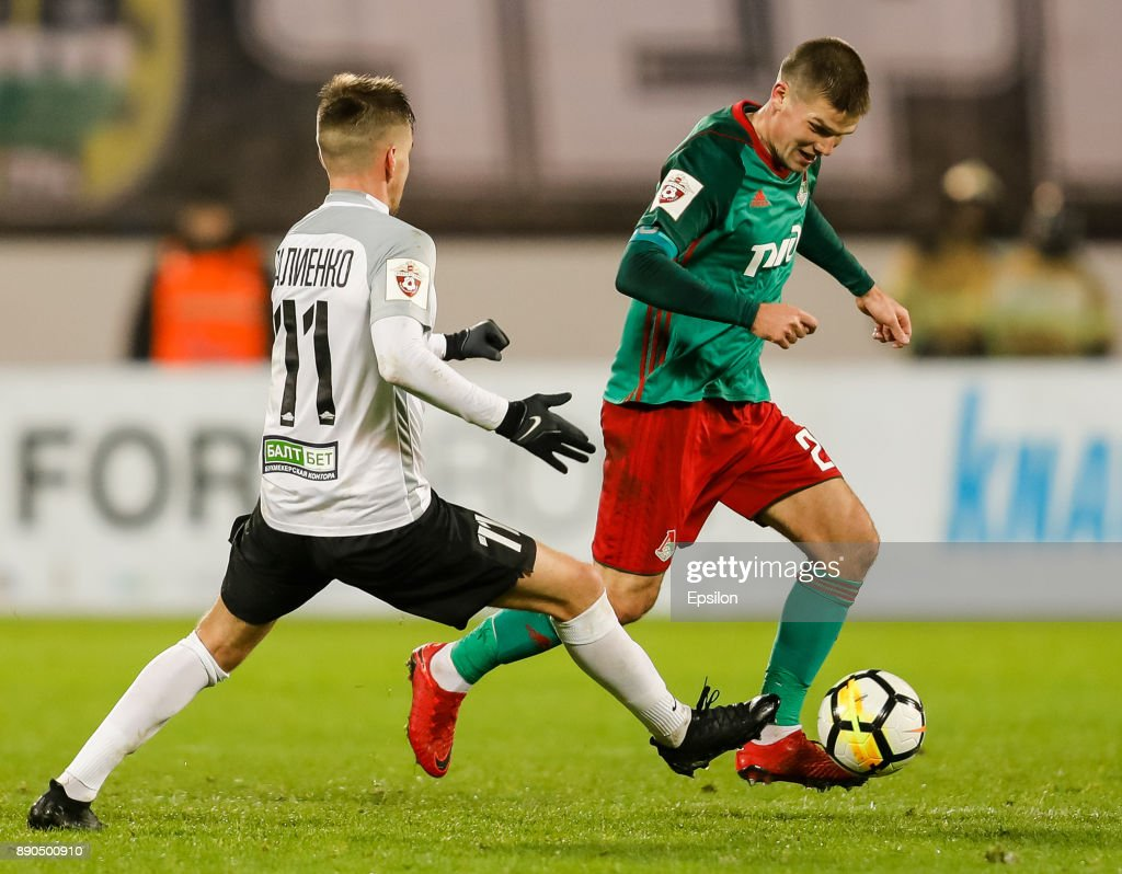 Maksim Paliyenko (L) of FC Tosno and Igor Denisov of FC Lokomotiv Moscow vie for the ball during the Russian Football League match between FC Tosno and FC Lokomotiv Moscow on December 11, 2017 at Petrovsky Stadium in Saint Petersburg, Russia.
