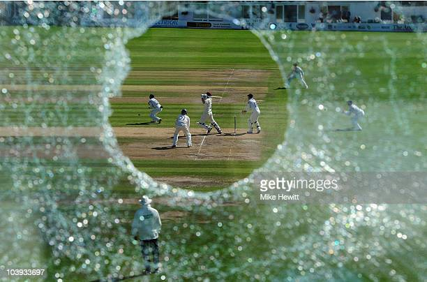 Mal Loye of Northamptonshire hits a boundary as seen through the hole in the press box window that he created with an earlier six, during the LV...