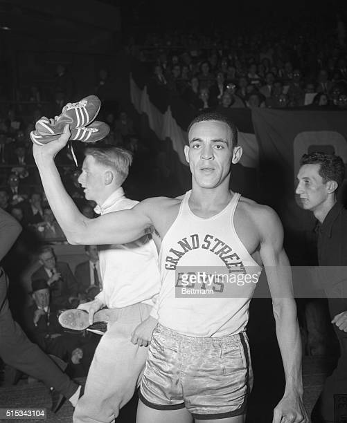 Mal Whitfield holds aloft the shoes with which he 'burned up' the track during the Knights of Columbus meet at Madison Square Garden Feb 28 He scored...