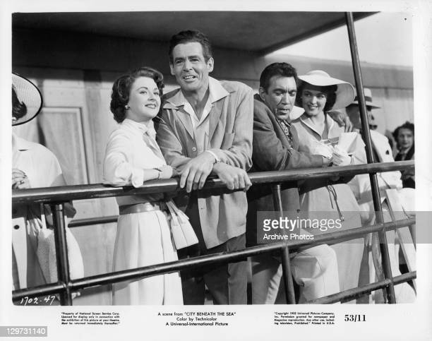 Mala Powers Robert Ryan Anthony Quinn and Suzan Ball standing together at railing in a scene from the film 'City Beneath The Sea' 1953