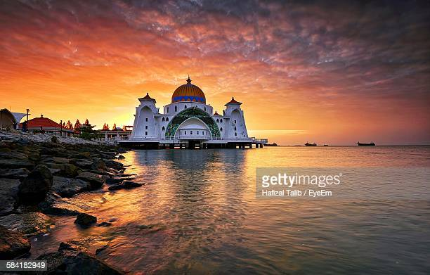 malacca straits mosque by sea against orange sky during sunrise - melaka state stock pictures, royalty-free photos & images