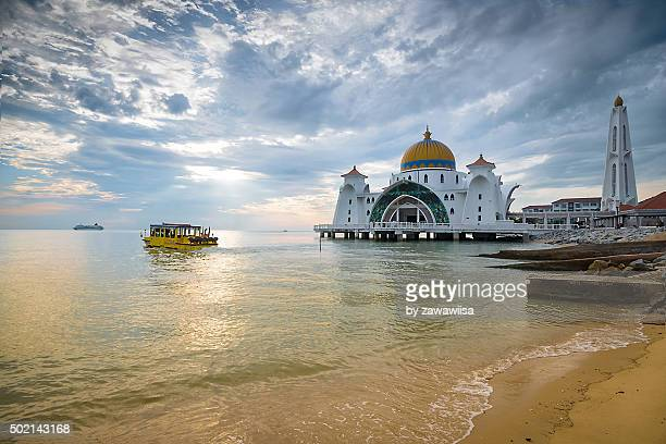 Malacca Straits Mosque 'Masjid Selat Melaka' near Malacca Town, Malaysia with water cruiser full of tourist enjoying scenery.