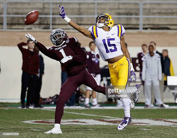 Malachi Dupre of the LSU Tigers leaps for the football as De'Vante Harris of the Texas AM Aggies defends in the first half of their game at Kyle...