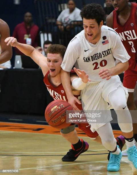 Malachi Flynn of the Washington State Cougars dives for a loose ball beating Jordan Schakel of the San Diego State Aztecs that lead to a basket in...