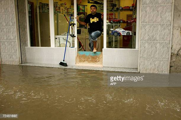 A shopkeeper looks at water flowing past his shop after heavy rainfall caused flooding in Torre del Mar near Malaga southern Spain 08 November 2006...