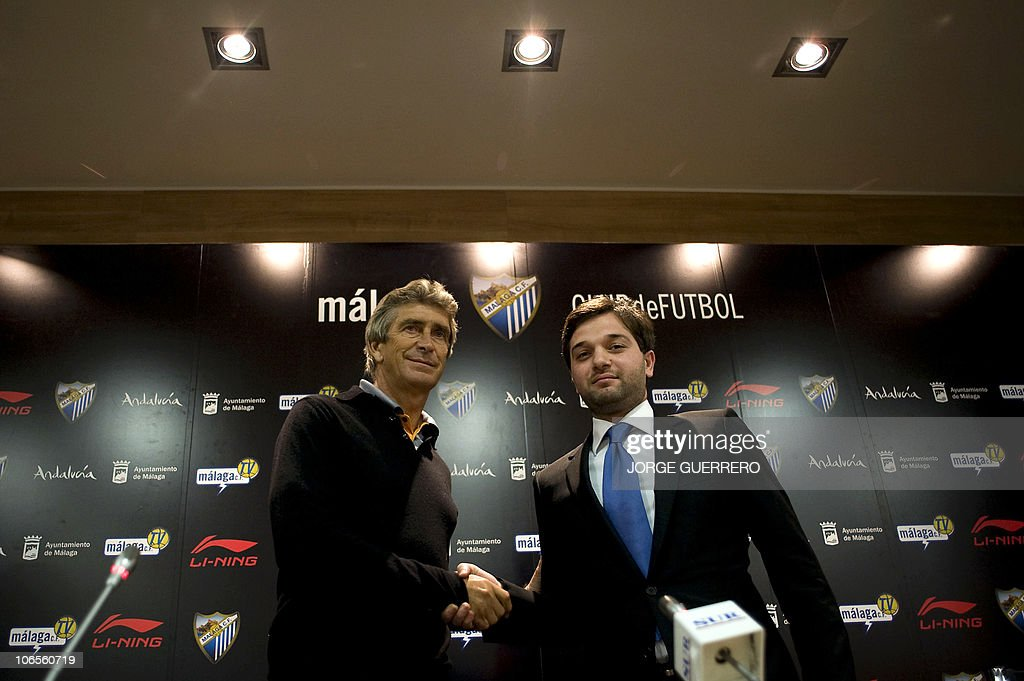 Malaga's Chilean new coach Manuel Pellegrini (L) shakes hands with Malaga's vice president Abdullah Ghubn prior to give a press conference during Pellegrini's official presentation at the Rosaleda stadium in Malaga, on November 5, 2010.
