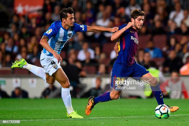 Malaga's defender Luis Hernandez challenges Barcelona's midfielder Sergi Roberto during the Spanish league football match FC Barcelona vs Malaga CF...