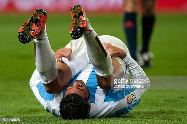 Malaga's defender Miguel Torres falls down during the Spanish league football match Malaga CF vs Club Atletico de Madrid at La Rosaleda stadium in...