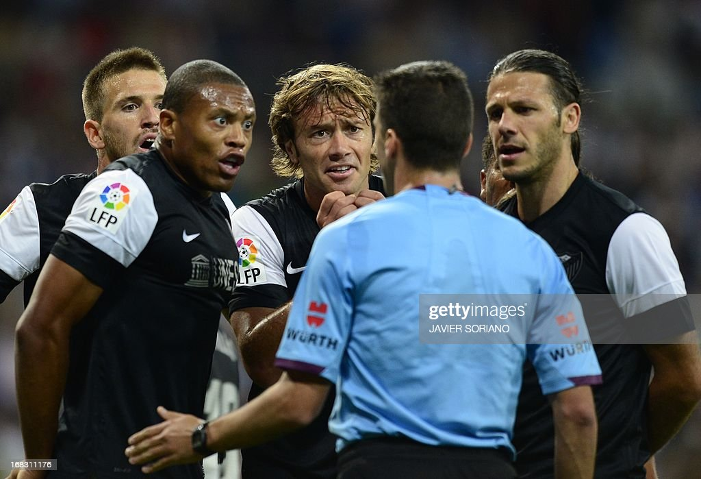 Malaga's football players argue with the referee during the Spanish league football match Real Madrid CF vs Malaga CF at the Santiago Bernabeu stadium in Madrid on May 8, 2013.