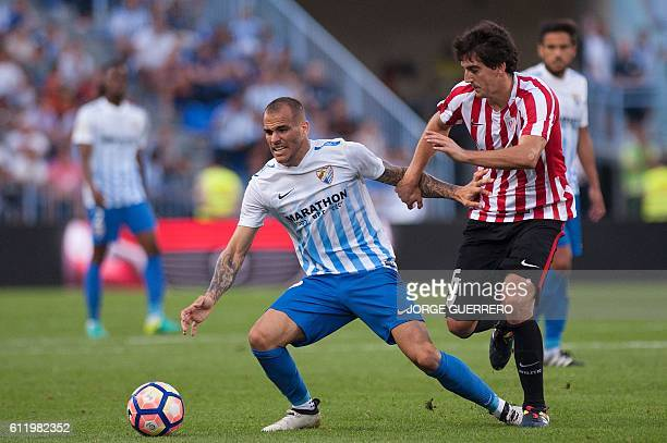 Malaga's forward Sandro Ramirez vies with Athletic Bilbaos defender Mikel San Jose during the Spanish league football match Malaga CF vs Athletic...