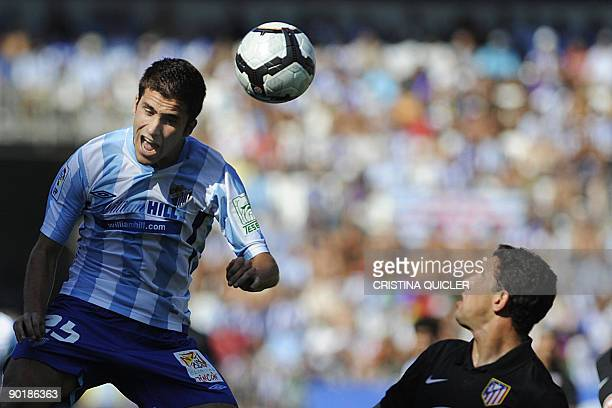 Malaga's Manu Torres fights for the ball with Atletico de Madrid's Maxi Rodriguez during their Spanish league football match at La Rosaleda stadium...