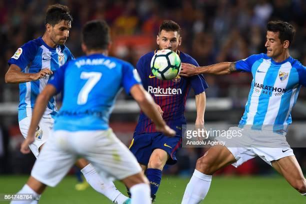 Malaga's midfielder Adrian Gonzalez Malaga's defender Juan Carlos Perez and Malaga's defender Luis Hernandez vies with Barcelona's Argentinian...