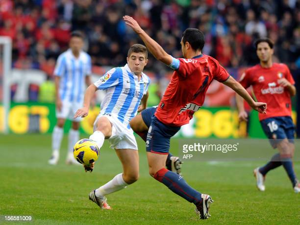 Malaga's midfielder Francisco Portillo vies with Osasuna's defender Miguel Flano during the Spanish league football match CA Osasuna vs Malaga CF on...