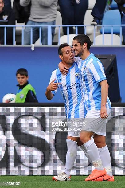 Malaga's midfielder Isco celebrates with midfielder Santiago Cazorla after scoring a goal during the Spanish league football match Malaga CF vs Real...