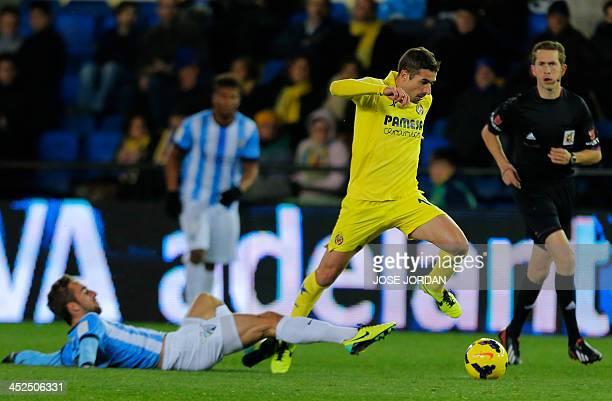 Malaga's midfielder Sergi Darder vies with Villarreal's midfielder Cani during the Spanish league football match Villareal CF vs Malaga at El...