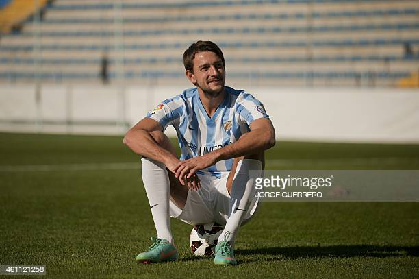 Malaga's new Belarus defender Igor Filipenko sits on a ball as he pose during his official presentation at the Rosaleda stadium in Malaga on January...