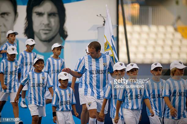 Malaga's new football player Dutch defender Joris Mathijsen walks with young Malaga's supporters during his official presentation at the Rosaleda...