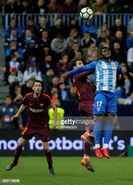 Malaga's Nigerian forward Isaac Success vies with Barcelona's Portuguese midfielder Andre Gomes under the eyes of Barcelona's Spanish midfielder...