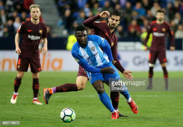 Malaga's Nigerian forward Isaac Success vies with Barcelona's Portuguese midfielder Andre Gomes during the Spanish league football match between...