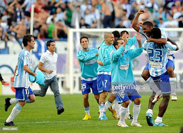 Malaga's players celebrates remaining in the first division during a Spanish league football match against Real Madrid at La Rosaleda's stadium in...