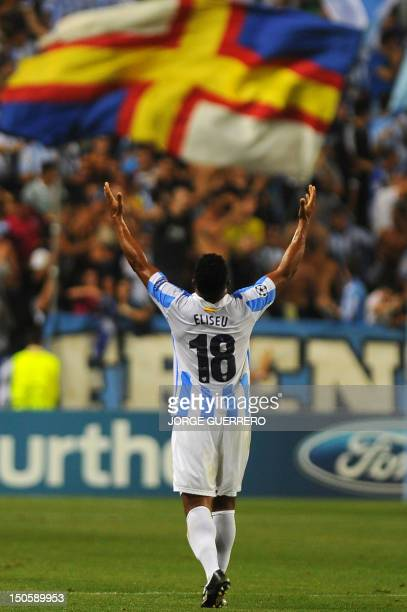 Malaga's Portuguese midfielder Eliseu celebrates after scoring during their UEFA Champions League playoff first leg football match Malaga CF vs...